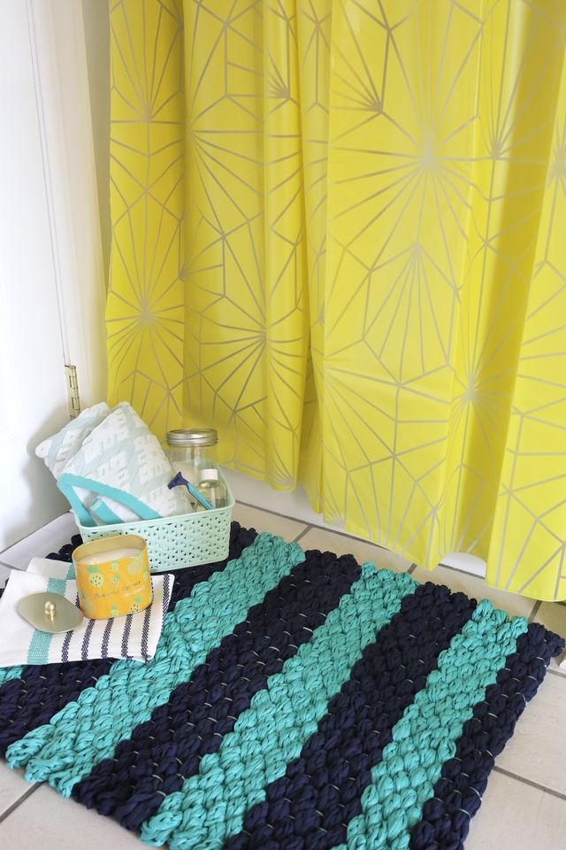 Create your own woven bath mat with finger-knit fabric yarn using this easy tutorial over at www.aBeautifulMess.com