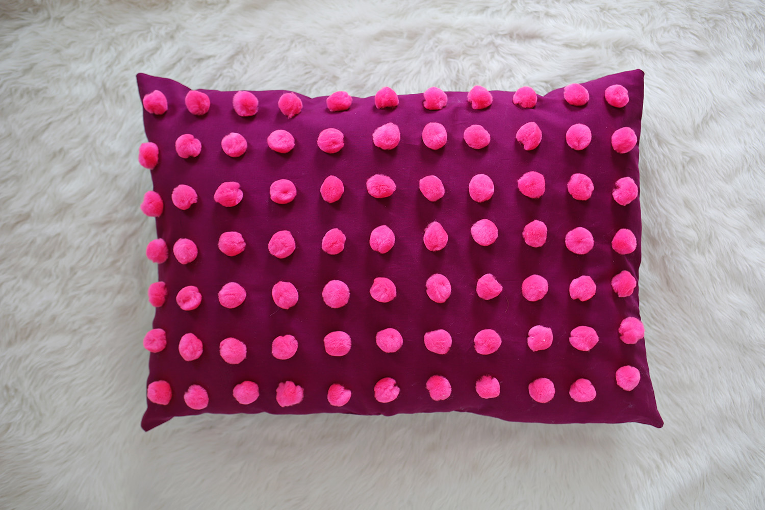 Plum pom pom pillow